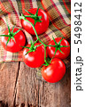 Fresh tomatoes on vintage wooden cutting board and linen towel