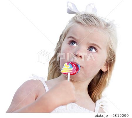 写真素材:Adorable Little Girl Enjoying Her Lollipop on White