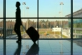 silhouette of woman walks against window at airport