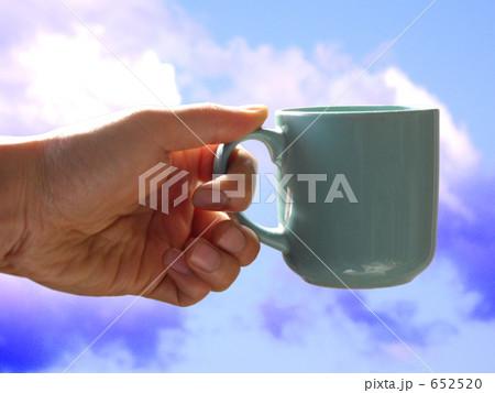 コーヒーカップを持つ手と青空 合成 652520