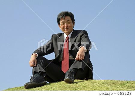 丘の上に座るミドルエイジ男性ビジネスマン 665228