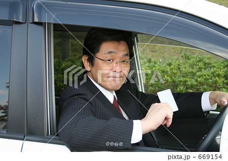 カードを差し出す運転席のミドル男性ビジネスマン 669154