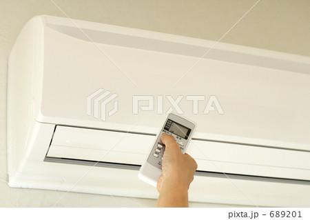 エアコンのリモコンを操作する女性の手 (作動前) 689201