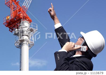 クレーンのある建設現場で働くスーツとヘルメットのミドルビジネスマン 1113679
