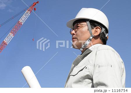 クレーンのある建設現場で図面を持つ作業服とヘルメットのミドルビジネスマン 1116754