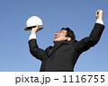 青空に向かって両手をあげて背伸びするスーツのミドルビジネスマン 1116755