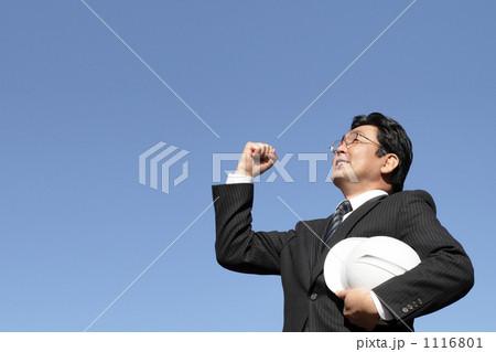 青空に向かってガッツポーズするヘルメットを持つスーツのミドルビジネスマン 1116801