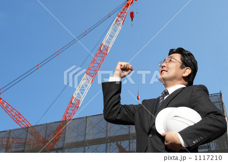 クレーンのある建築現場でガッツポーズするヘルメットを持つスーツのミドルビジネスマン 1117210