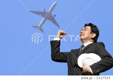 青空の飛行機にに向かってガッツポーズするヘルメットを持つスーツのミドルビジネスマン 1117524