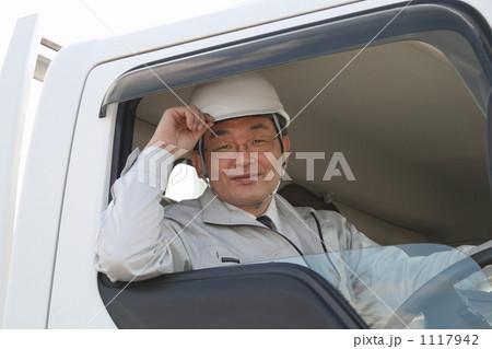 運転席で笑顔で挨拶する作業服の働くミドルドライバー 1117942