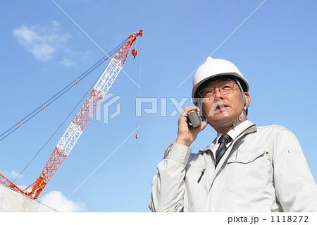 クレーンのある建築現場で無線交信をするミドルビジネスマン 1118272