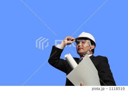 設計図面を持つヘルメットとスーツ姿のミドル ビジネスマン(切抜きブルーバック) 1118510