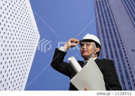 設計図面を持ちビルの谷間に立つヘルメットとスーツ姿のミドル ビジネスマン 1118511
