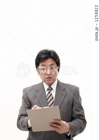 メモボード(書類・問診票)に記入する男性ミドルビジネスマン 1258822