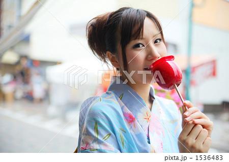 りんご飴を食べる女性 1536483