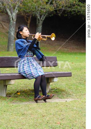 公園のベンチに座ってトランペットを吹く若い女性 1976600