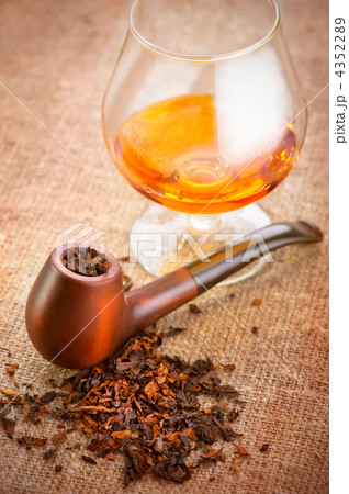 Glass of cognac and pipe with tobacco on linen canvas backgroundの写真素材 [4352289] - PIXTA