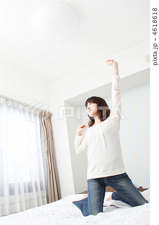 ベッドの上で膝立ちをして背伸びをしている女性 4618618