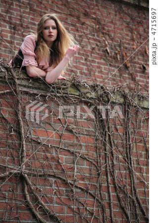 レンガのバルコニーから物憂い気にこちらの様子を見下ろす外国人女性(編集前) 4715697
