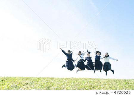 草原でジャンプをする中学生