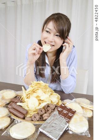 スナック菓子を食べながら電話をかける女性 4822450