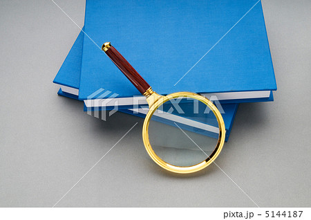 Magnifying glass over the stack of booksの写真素材 [5144187] - PIXTA
