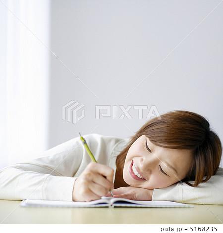机に伏せながらノートに書き込む女性の写真素材 5168235 Pixta