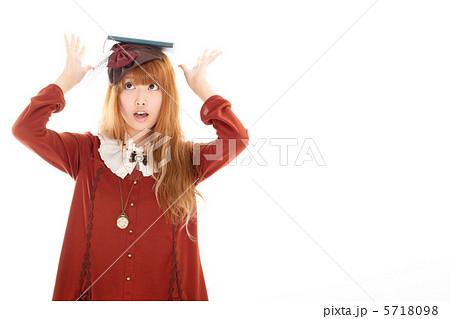本を頭の上に乗せてバランスを取って遊ぶ少女 5718098