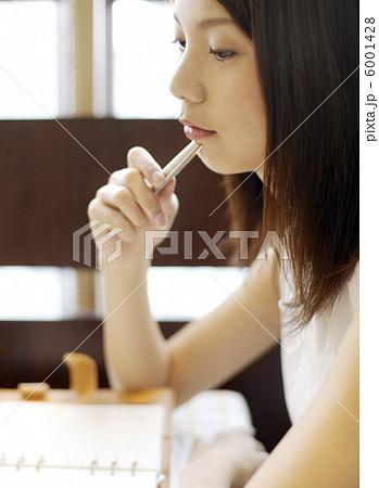 ペンを口元にあてる女性 6001428