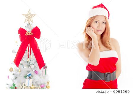 クリスマスツリーとちょっと色っぽいポーズをするセクシーな女性のサンタさん 6061560
