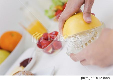 グレープフルーツを搾る女性の手...