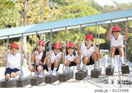 遊具で遊ぶ体操服姿の小学生の写...