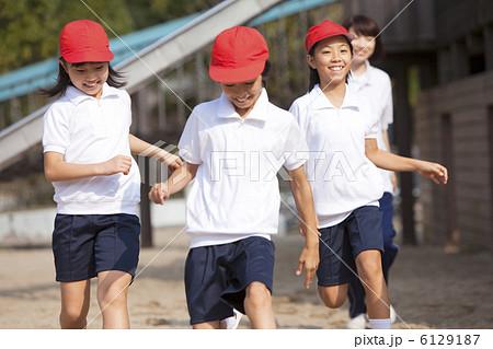 走る体操服姿の小学生と先生の写...