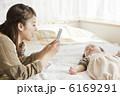 赤ちゃんの寝顔をスマートフォンで撮影する母親 6169291