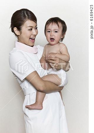 泣いている赤ちゃんを抱いた看護師の写真素材 [6169425] - PIXTA