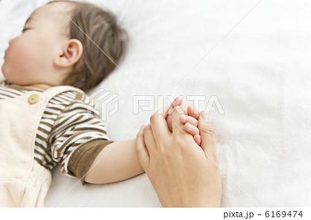 母親の手を握って寝ている赤ちゃん 6169474