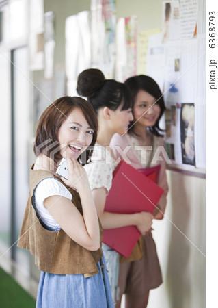 笑顔の女子大生と掲示板を見ている女子大生2人 6368793