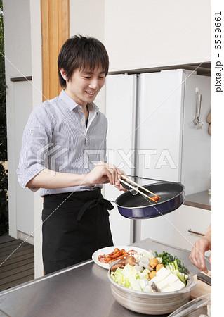 料理をフライパンから皿に移す男性 6559661