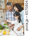 シニア夫婦の料理を手伝う孫娘 6570804