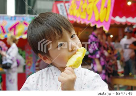 屋台と冷やしパインを食べる子供 6847549