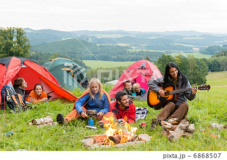 Camping students listening girl with guitar tents 6868507