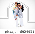 Happy family standing with a white house illustration on a white 6924931