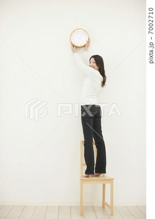時計を掛ける女性の写真素材 [7002710] - PIXTA