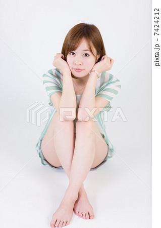 膝を抱えて座る若い女性(正面) 7424212