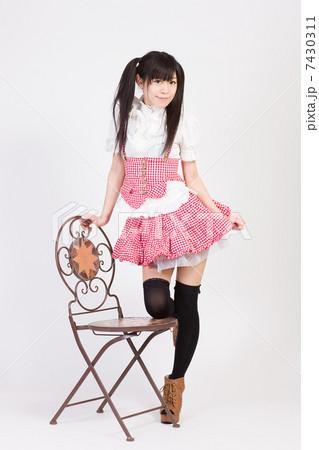 椅子に膝をついて立つ若い女性 7430311