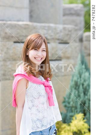 野外で笑顔の若い女性 7478282