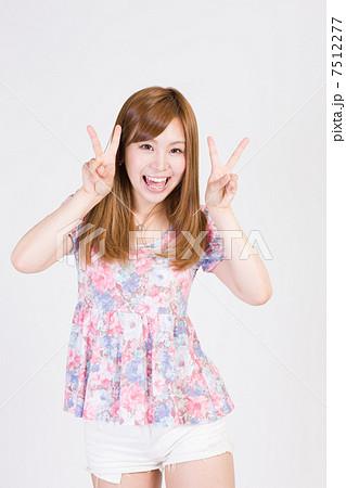 両手でVサインをする笑顔の若い女性 7512277