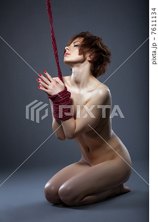 Sensual nude model posing tied with rope 7611134