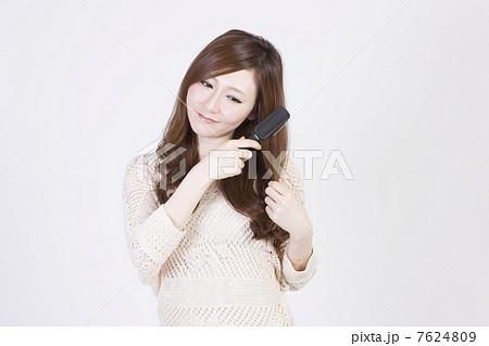 ブラシで髪を解く若い女性2 7624809
