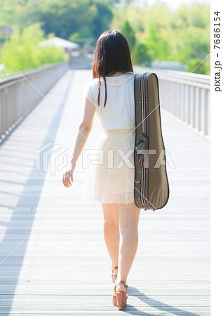バイオリンケースを背負って歩く女性の後ろ姿 7686154
